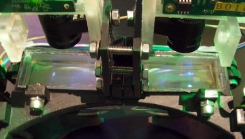 写真の中央部に見える2つの透明な物体が、作製工程に3Dプリンターを適用した光学部品(撮影:日経 xTECH)