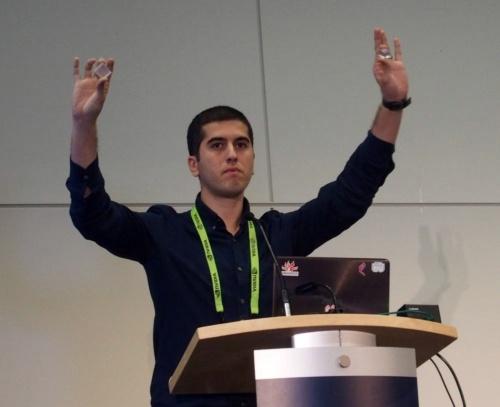 NVIDIAのKaan Aksit氏が講演。3Dプリンターなどで作製した光学部品を手に持っている(撮影:日経 xTECH)