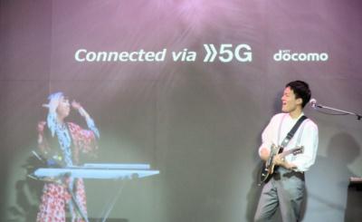 NTTドコモの「5G Cyber Jam Session」の様子。左側のバンドメンバーは、ブース内のステージから離れた場所にあるボックス内で演奏している