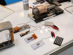 図1 金沢大学の研究チームが開発した振動発電装置、全長15~20mmの小型モデルは写真下部にある(撮影:日経 xTECH)