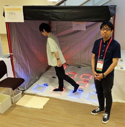 ゼミ生が作成したゲーム機「TILE TILE」と、橋本直准教授(右)