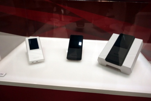 5G対応ルーター。左の2つがルーター本体、右はWi-Fi接続を強化するためのクレードルが付いたもの。本体の外形寸法は140mm×73mm×25mm、質量は200g。2.6型液晶ディスプレーを備える。バッテリー容量は6400mAh。OSは「Android 10.0」。プロセッサーSoCは米クアルコム(Qualcomm)の「Snapdragon 865」(5Gモデム「Snapdragon X55」搭載)。nano SIMスロットを備える。(写真:日経 xTECH)