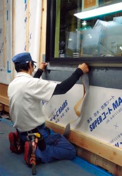 サッシまわりの防水テープ施工。作業環境が工場内で常に安定しているので、こうした作業の施工精度も高い(写真:大菅 力)