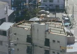 日経ホームビルダーの取材で、屋根材を飛散させたのは現場から約150m離れた3階建ての建物と判明。陸屋根の屋上に木製の支柱を立て、折板屋根を載せていた(写真:日経ホームビルダー)