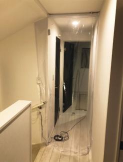 療養室ゾーンと清浄ゾーンを2重のビニールカーテンで仕切っている様子。開け閉めが必要な箇所以外の隙間はできるだけ塞ぐ(写真:山本 佳嗣)