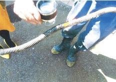 間仕切り壁の床下に敷設されていたガス管。消防隊員は被覆が燃えて黒くなっている箇所に、直径1mm未満のピンホールを発見した(写真:住民から提供)