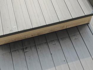 氷が屋根の一段高い箇所から落下し、真下にある屋根葺き材がへこんだ状態(写真:樋口板金)