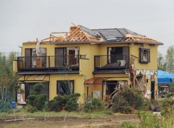 築19年目の木造2階建て住宅を、竜巻の進行方向に沿って見る。ひねり金物で所々留められていた小屋組み材が飛散した。1階の右側面には高い位置に出窓が付いていた。この側面は、雨戸を閉めていた面とは異なる壊れ方をしていた(写真:日経ホームビルダー)