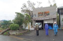 潤井戸地区で金属製折板屋根がまるごと吹き飛んだ木造2階建て倉庫。1階に設置されていた軽量シャッターのスラットが、ガイドレールから外れていた(写真:日経ホームビルダー)