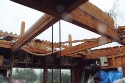 タイトフレームで桁に留めていた倉庫の金属製折板屋根が吹き飛んでいる様子。竜巻の風圧力でビスが破断していた(写真:日経ホームビルダー)