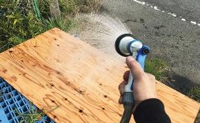 試験体に取り付ける前の合板に、シャワーホースで水を掛けた(写真:日経ホームビルダー)