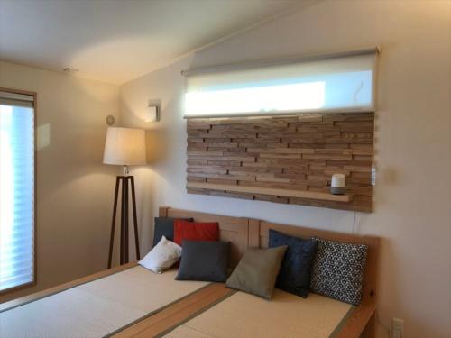 2階の寝室。左の窓の屋外ブラインドは宅外操作ができ、音声制御もできる。スタンド照明は音声制御ができる(写真:日経 xTECH)