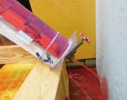5年前の実験では、45度の傾斜を付けた全長1.5mの試験体を制作。下地木材に防水紙と金具を取り付け、試験体を半円形のアクリルパイプで覆って、内部に20分間液体を流した。下端の金具には1000mmの水頭圧が掛かる。当時の研究メンバーは、梅田次長のほかに東海大学の石川廣三名誉教授、国土技術政策総合研究所の宮村雅史・主任研究官、住宅瑕疵担保責任保険協会の木村雄太氏、日本防水材料連合会の牧田均氏(役職は当時)の計5人(写真:梅田 泰成)