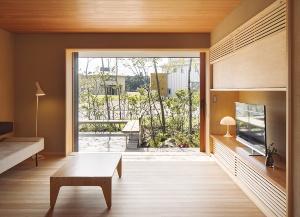 リビング。障子と木製サッシを引き込めば室内とテラスが一体化する。窓と障子を閉じると夏でも室内の温度は均一に(写真:浅田 美浩)