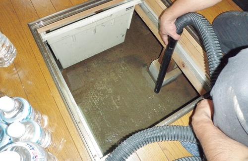 〔写真1〕乾湿両用掃除機で吸い取る