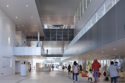 建物内ながら街を歩くような感覚が得られる「tette通り」。敷地の高低差に合わせて床は緩いスロープで、東から西に向かって低くなる。この通路は1m2当たり5円/時間の使用料で場所貸ししていて、イベントや展示を行うことが可能。3~4階に鉄骨トラスによる大断面構造の床をつくり、2階の床の張り出し部分は上から吊り、1階の通路に柱が落ちないようにした(写真:吉田 誠)