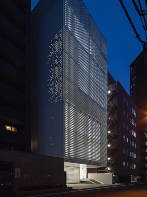 中小規模のオフィスビルやマンションが立て込む街なかに立つ。小さな穴の開いたファサードは、オフィス内の照明が近隣を照らし出すのを抑えている(写真:井上 登)