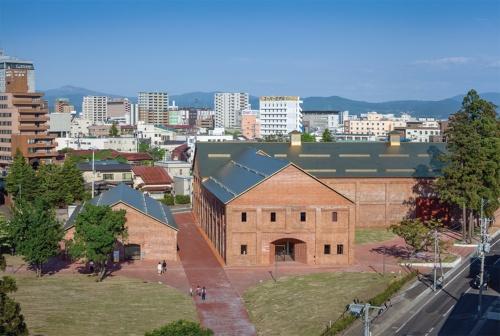 写真右が「ミュージアム棟」、左が「カフェ・ショップ棟」。ミュージアム棟の入り口には、レンガをずらした「弘前積み」と呼ぶ積み方を用いた。建物の間に「ミュージアム・ロード」を配置して回遊性を高めた。チタンの菱ぶき屋根は、光の加減で様々な表情を放つ(写真:吉田 誠)