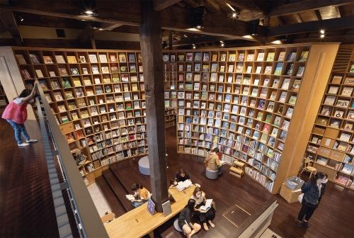 閲覧室Cをギャラリー(空中廊下)から見下ろす。大黒柱を中心に円弧状の大きな書棚が取り巻く。子どもの手の届かない高さに飾られた本は、必ず低い位置に同じ本がある(写真:吉田 誠)