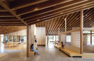 西側のギャラリーから、ささゆりホールがある東側を見通したところ。左手に見えるテーブルが置かれたエントランスホールや、図書スペース(右奥)、託児・乳児室(右手前の障子部分)などが一体的につながる。床はモルタル磨き仕上げの土間、スギ圧縮フローリングなどで変化を付けて空間を分節している(写真:吉田 誠)