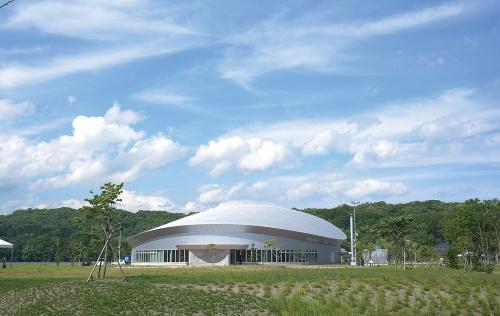 体験交流ホール外観。金属の曲面屋根で覆われた体験交流ホールはアトリエブンク・総合設備計画JVの設計だ。半円形のスラスト型ステージに客席500席以上を備える(写真:船戸 俊一)