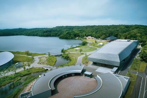 南側上空から見た「民族共生象徴空間(ウポポイ)」の全景。ポロト湖を囲むように施設を配した。写真左に一部屋根が写るのが「体験交流ホール」で、手前がエントランス棟。右奥が「国立アイヌ民族博物館」だ(写真:丹青社、日展、フォワードストローク)