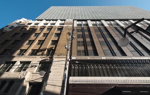 本館南面、清水通り側見上げ。左側が1932年の第3期工事から残っているとみられる外壁。新しい外壁も、これになじむ3層構成とした(写真:生田 将人)