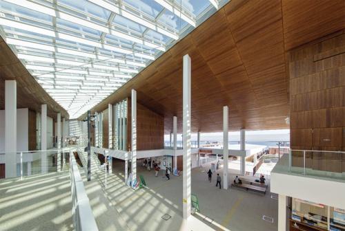 宮島の玄関口に当たる宮島口に完成したフェリーターミナル。2枚の大きな屋根がトップライトを挟んで切妻状に架かり、半屋外の開放的な空間が広がる。宮島口と宮島桟橋を結ぶ「宮島航路」は、宮島を訪れる観光客の大半が利用するほか、宮島の住民にとって生活の足でもある(写真:イクマ サトシ)