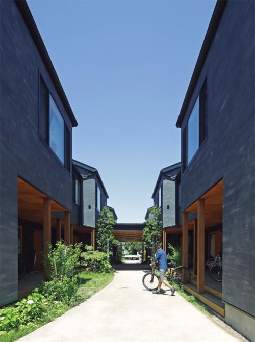 住棟の真ん中を路地が貫き、一部は屋根付きの広場のようになっている。路地の両側にウッドデッキのポーチ、その奥に各住戸の玄関がある。写真は13戸が入る1期の「椚(くぬぎ)棟」。2017年10月に完成した(写真:安川 千秋)