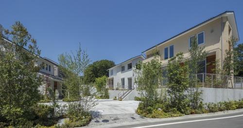 「クラスターコモン」越しに住宅を見た様子。先行する第1期は2018年8月に工事が完了。10月から販売を開始する(写真:アキュラホーム)