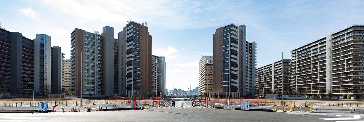 HARUMI FLAGの中心軸になる道路を、「中心広場」の真ん中から南西方向に見た景色。向かって左が「PARK VILLAGE」、右が「SUN VILLAGE」。手前の2つの空き地には、24年にタワー棟が立つ。2020年2月に撮影したもの(写真:北山 宏一)