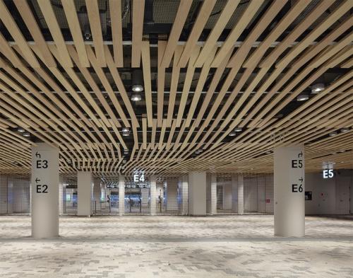 1階南側のエントランス。天井は軒庇から回り込むように木のルーバーが続く。スタンドへの動線は外部ゲートで各層のエントランスを分ける計画とし、コンコースでの上下移動を少なくした。イベントによって3層目だけ閉鎖する使い方も可能だ(写真:吉田 誠)