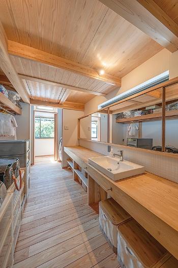 隣の洗面洗濯室の奥に、トップライト付きの物干し場を配置した。冬はセンサー付きの換気扇を通して、日射で得た熱と洗濯物が発する水蒸気を、物干し場から寝室に送り込む(写真:車田 保)