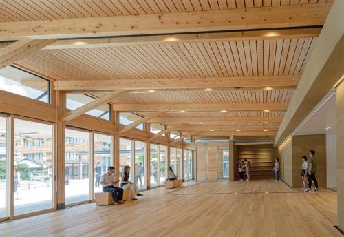 広さ約200m2のエントランス棟。長さ4mのヒノキ製材を軸方向に2本継ぎ、さらに2段の重ね梁として8mのスパンを飛ばした。全面開放できる開口部には、120mm角のヒノキ製材4本による組み柱が並ぶ(写真:時空アート)