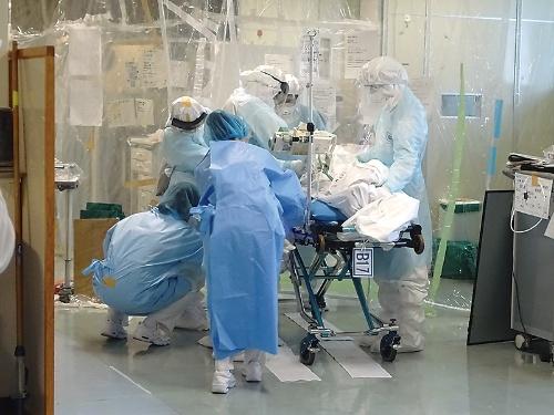 旧病棟のICU(集中治療室)で、新病棟に引っ越すために新型コロナの患者を運び出そうとしている様子(写真:横浜市立市民病院)