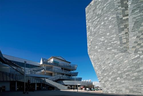 2階レベルにある中央広場を取り囲むように、6階建ての「本棟」(写真左から中央)と「角川武蔵野ミュージアム」が立つ。右手に見えるミュージアムの外壁は、約2万枚の石を張っている(写真:安川 千秋)