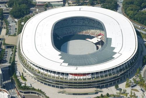東京五輪・パラリンピックのメインスタジアムの国立競技場。「杜(もり)のスタジアム」がコンセプトで、木材を内外に多用したのが特徴だ。観客席は「木漏れ日」をイメージして5色の椅子がモザイク状に配された。大会後はコンセッション(運営権売却)方式の導入などが検討されているが、利用計画は明確に決まっていない。競技場を管理・運営する日本スポーツ振興センター(JSC)は2021年6月18日、民間事業化に向けたアドバイザリー業務の委託について企画競争を公告した。国立競技場のある神宮外苑地区では、秩父宮ラグビー場の移転整備など再開発事業も動き出す(写真:共同通信社)