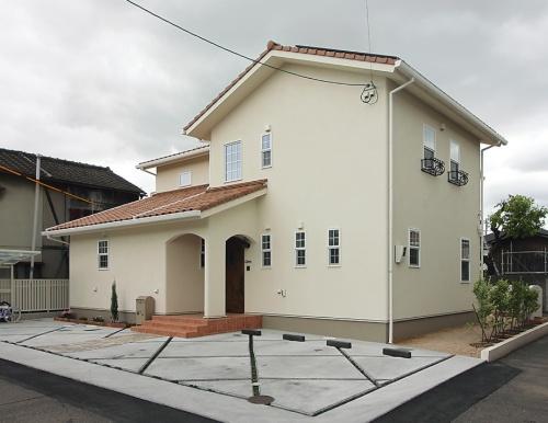 U邸の外観。西洋瓦とアクリル樹脂系の仕上げ塗り材で仕上げている。災害対策を意識して屋根には約4kWの太陽光発電パネルを載せている(写真:日経アーキテクチュア)
