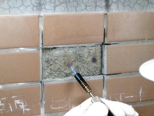吸水調整材を塗り過ぎていたコンクリート面を、トーチバーナーであぶっている様子。塗膜が厚い箇所は、濃い茶褐色になった(写真:鈴木哲夫設計事務所)