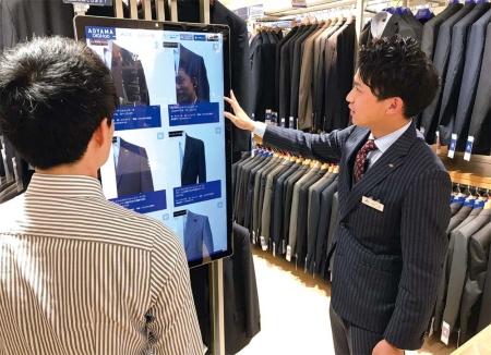 青山商事の新型店舗「デジタル・ラボ」では販売スタッフが大型タッチパネルで来店客の好みの商品を探す。デジタル・ラボは2019年11月時点で38店舗を展開する