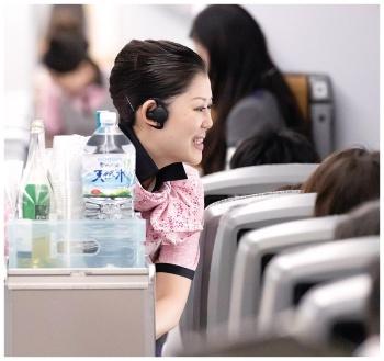 客室乗務員は片耳にBluetoothイヤホンマイクを装着する(写真提供:全日本空輸(客室乗務員))