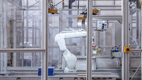 倉庫に届いた荷物をロボットアームが取り出し、バーコードを読み取って専用コンテナに載せる(写真提供:京東集団)