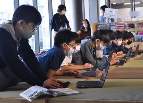 端末1人1台の環境で学ぶドルトン東京学園中等部の生徒の様子。校内はどこでも無線LANがつながる。生徒は思い思いの場所で調べ学習をしている