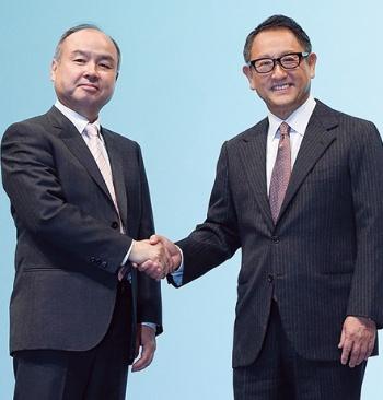 提携を発表し握手するソフトバンクグループの孫正義会長兼社長(左)とトヨタ自動車の豊田章男社長(写真:村田 和聡)