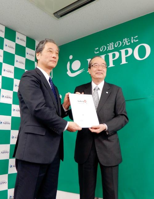 写真1■ IGSAPの向殿政男会長(右)が、NIPPOの荒井明夫総合技術部長(左)にSafety2.0適合証明書を手渡した(写真:三上 美絵)