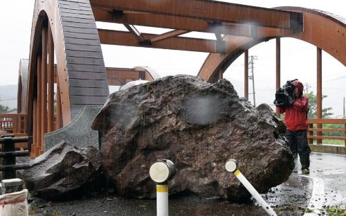 写真3■ 村上市の市道に落下した巨石。後ろに見えるアーチは、旧山北町が2002年に架け替えた八幡橋。6月19日に撮影(写真:日本経済新聞社)