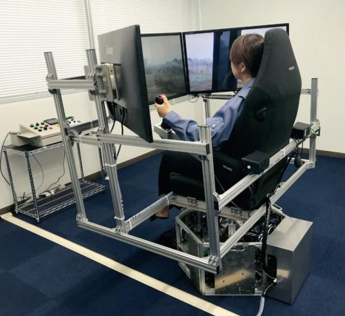写真2■ 遠隔操作室。座席の下の3自由度モーションベースで建設機械の動きを再現する(写真:熊谷組)