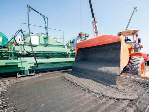 写真1■ 実証実験でコンクリート床版にUHPFRCを打設している様子。実現場を想定し、劣化が進んだコンクリート床版の一部をはつった後の鉄筋が露出した状態を再現した。UHPFRCは極めて緻密なセメント系材料を繊維で補強している。水結合材比は15%程度だ。UFCで必須の蒸気養生は行わず、通常の現場養生で事足りる(写真・資料:鹿島)