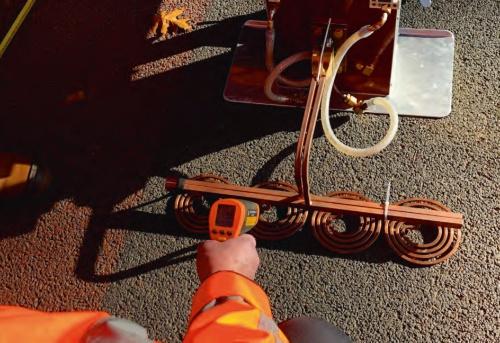 写真1■ オランダで自己治癒型のアスファルト舗装を施工してから5年後に、供用状況を確認している様子。舗装表面に特殊機器を当てて加熱するだけで、劣化を修復できる(写真:山田 敏広)