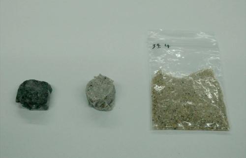 写真1■ ケイ砂から製造した硬化体(左の2つ)と原料のケイ砂。中央がアルコールと触媒を混ぜて製造した硬化体で、左はこれをさらに加熱して強度を高めた(写真:日経クロステック)
